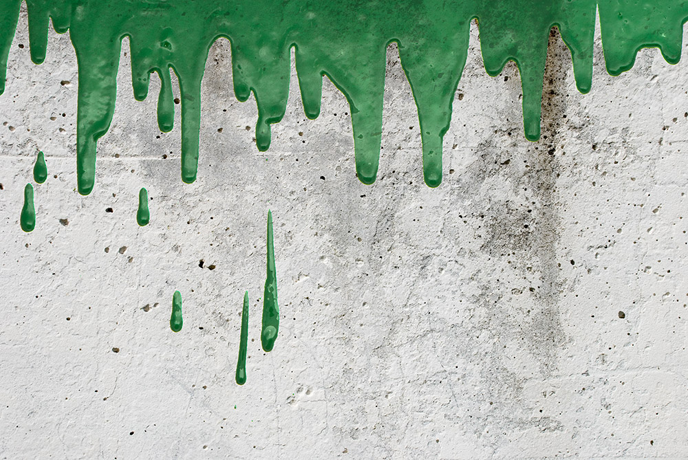 Green paint pouring on vintage wall background